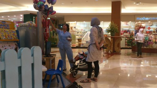 h mum with baby buying toys