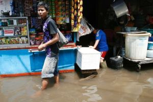 jakarta flood 2013 man standing in water small store in the background