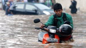 jakarta flood 2013 motorbike man in knee-deep water, indonesia floods